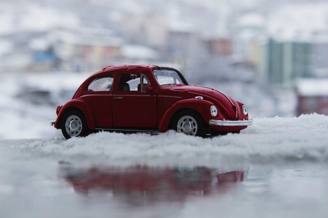 A miniature red car is nestled in snow